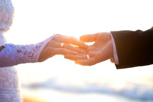 Holding Hands with wedding rings on the background of sea and sun. - A.KaZaK