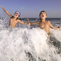 Children Playing in the Sea - Michelangelo Gratton / Shutterstock