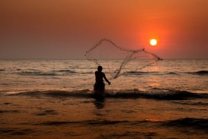 A Goan fisherman casts his net at sunset- John Foreman