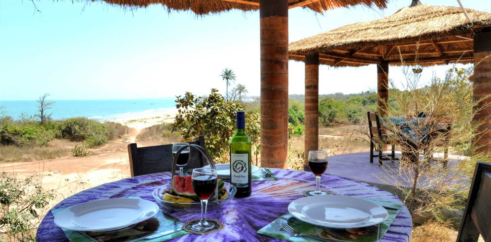 Thatched cabanas with a view of the ocean at Tanji Eco-Lodge, Gambia