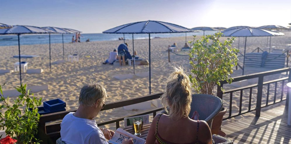 Watch the sunset while enjoying a cocktail at the beach bar at Hotel Morabeza, Santa Maria, Sal