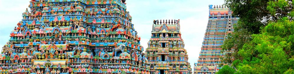 Beautiful view of colorful gopura in the Hindu Jambukeswarar Temple against the background of cloudy blue sky in Trichy (Tiruchirapalli), Tamil Nadu, South India - Natalia Davidovich | Shutterstock