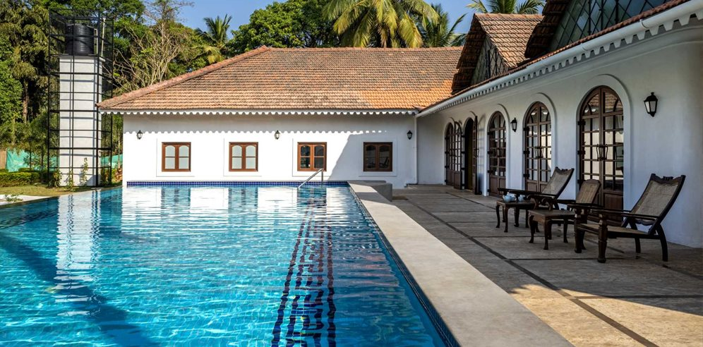 Swimming pool and sunloungers at The Postcard Cuelim, South Goa
